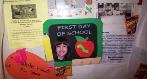 child's school work displayed on refrigerator
